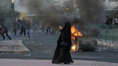 Жительница Бахрейна фотографирует сотрудников полиции во время антиправительственных демонстраций в Бахрейне. Архивное фото