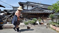 Женщина у своего разрушенного в результате землетрясения дома. Кумамото, Япония. Апрель 2016
