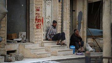 Мужчины сидят на крыльце дома на одной из улиц Пальмиры