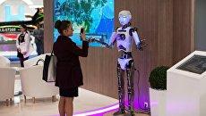 Девушка фотографирует робот Теспиан на выставке SPIEF Investment & Business Expo