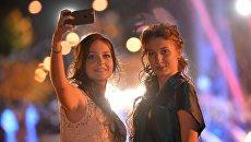 Выпускники московских школ фотографируются на мобильный телефон во время празднования Последнего звонка