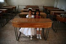 Девочки сидят за партой в одной из школ в Дамаске. Сирия, 21 мая 2016
