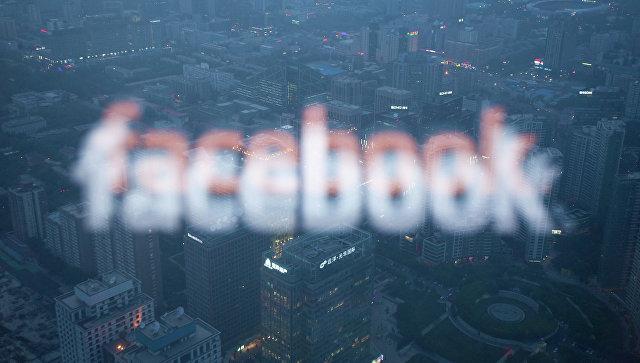 Логотип социальной сети Facebook в отражении экрана монитора компьютера в окне. Архивное фото