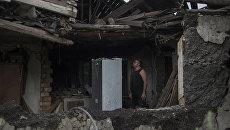 Местный житель в своем доме, разрушенном в результате обстрела. Архивное фото