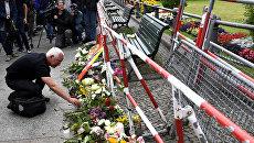 Человек оставляет цветы перед посольством Франции в Берлине. 15 июля 2016 года