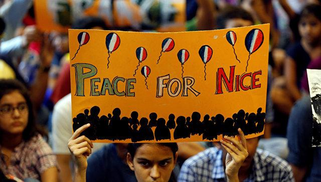Девочка держит плакат во время молитвы о жертвах теракта в Ницце