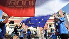 Молодые люди держат флаги Польши и Евросоюза во время демонстрации в Варшаве. Архивное фото