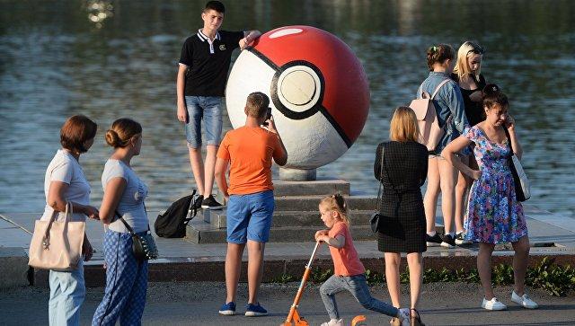Прохожие рядом с гигантским покеболом из компьютерной игры Pokemon Go от компании Nintendo на набережной городского пруда в Екатеринбуре. Архивное фото