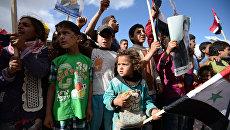 Жители населенного пункта Каукаб в Сирии во время раздачи российской гуманитарной помощи. Архивное фото