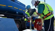Сотрудники АЗС берут пробу бензина во время приемки бензовоза. Архивное фото