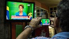 Мужчина записывает выступление по бразильскому телевидению временно отстраненной от должности Дилмы Роуссефф. Архивное фото