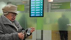 Женщина считает деньги в отделении Сбербанка России