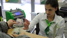 Женщина расплачивается в кассе отделения банка. Архивное фото