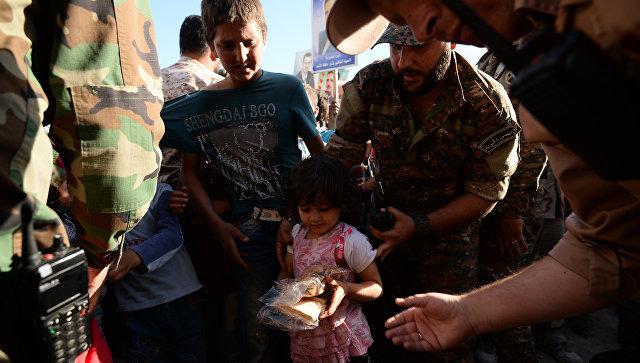 Жители населенного пункта в Сирии во время раздачи гуманитарной помощи. Архивное фото