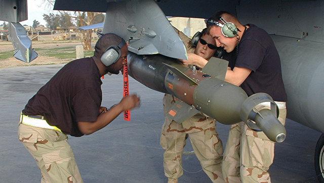 Американские военные закрепляют бомбу на крыле истребителя F-16. Архивное фото
