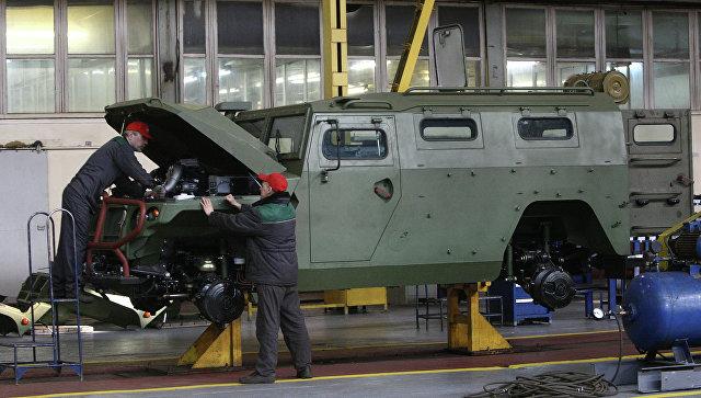 Рабочие осматривают военный бронеавтомобиль Тигр
