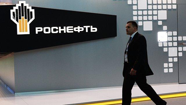 Посетитель проходит у павильона компании Роснефть . Архивное фото