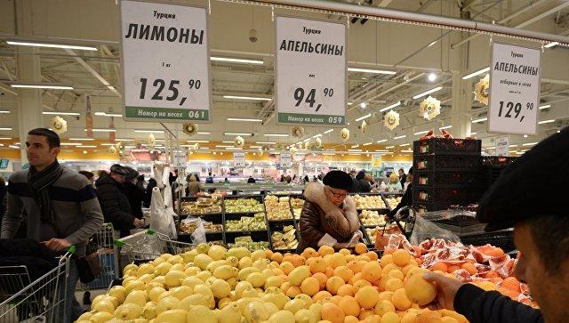 Покупатели у прилавка с лимонами и апельсинами из Турции в торговом зале. Архивное фото