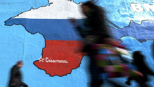 Прохожие у нарисованной на стене карты Крыма в цветах российского флага. Архивное фото