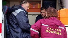 Медработник оказывает помощь спасенным членам экипажа плавучего крана, затонувшего у берегов Крыма, в порту Балаклавы
