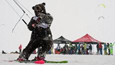 Спортсмен в костюме медведя во время гонок в дисциплине фристайл в рамках кубка Сибири по зимнему кайтингу на льду водохранилища Новосибирской ГЭС