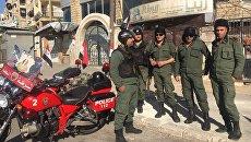 Полиция у гуманитарного коридора Бустан аль-Каср в восточном Алеппо в ожидании выхода боевиков и мирных граждан