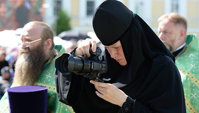Монахиня с фотокамерой во время литургии