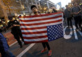 Участник акции протеста против избранного президента США Дональда Трампа с перевернутым флагом США в Сан-Франциско