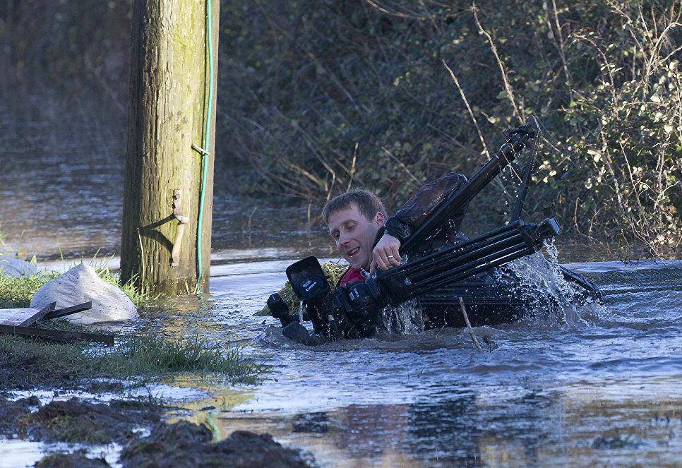 Телеоператор во время съемок операции по оказанию помощи пострадавшим от наводнений в Вересковой пустоши, Великобритания