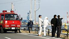 Пожарные и местные жители смотрят на море после предупреждения о возможном цунами в городе Сома, Япония