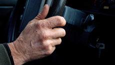 Рука пожилого мужчины на руле автомобиля. Архивное фото