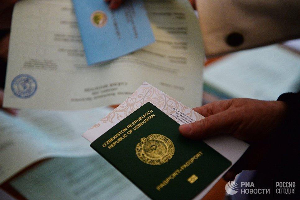 Паспорт и бланк в руках избирателя во время выборов президента Узбекистана