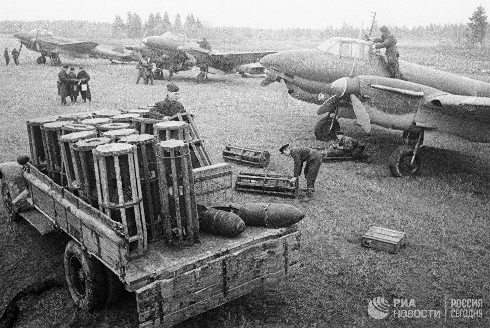Бойцы разгружают грузовик с бомбами на военном аэродроме.