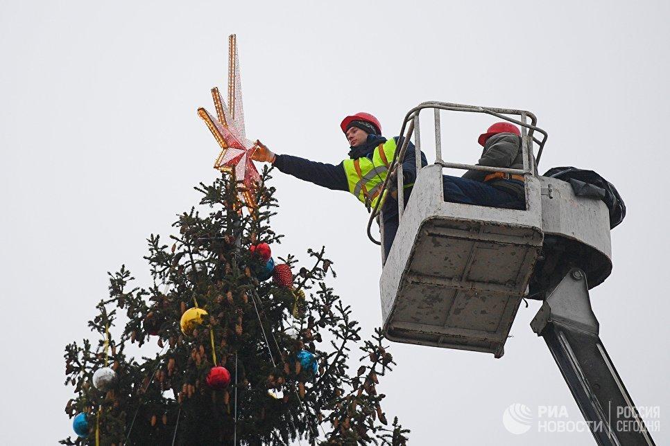 Рабочие украшают Новогоднюю ёлку на Соборной площади Кремля в Москве