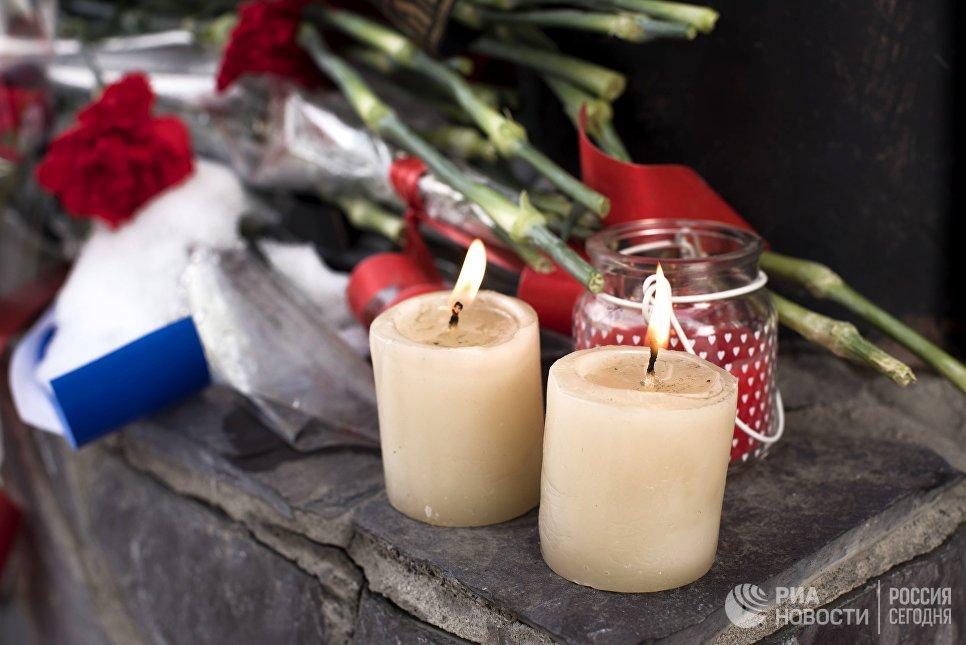 Цветы и свечи у посольства России в Бишкеке в память о погибших при крушении самолета Ту-154