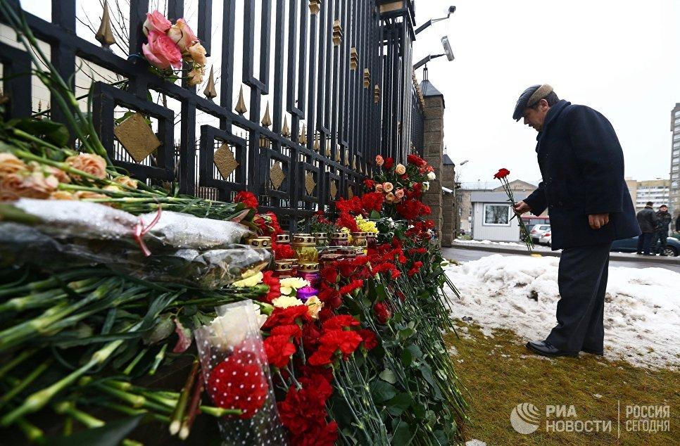 Мужчина возлагает цветы в память о погибших в авиакатастрофе Ту-154 в Сочи у посольства России в Минске