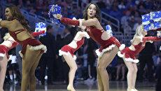 Танцовщицы Орландо Мэджик выступают в рождественских костюмах во время баскетбольной игры NBA против Мемфис Гриззлис в Орландо, США