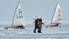 Рыбаки (на первом плане) и участники открытых соревнований по буерному спорту на кубок командующего Тихоокеанским флотом на льду Амурского залива во Владивостоке