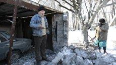 Местные жители возле гаража, пострадавшего в результате обстрела украинскими силовиками, в городе Макеевка Донецкой области. Архивное фото