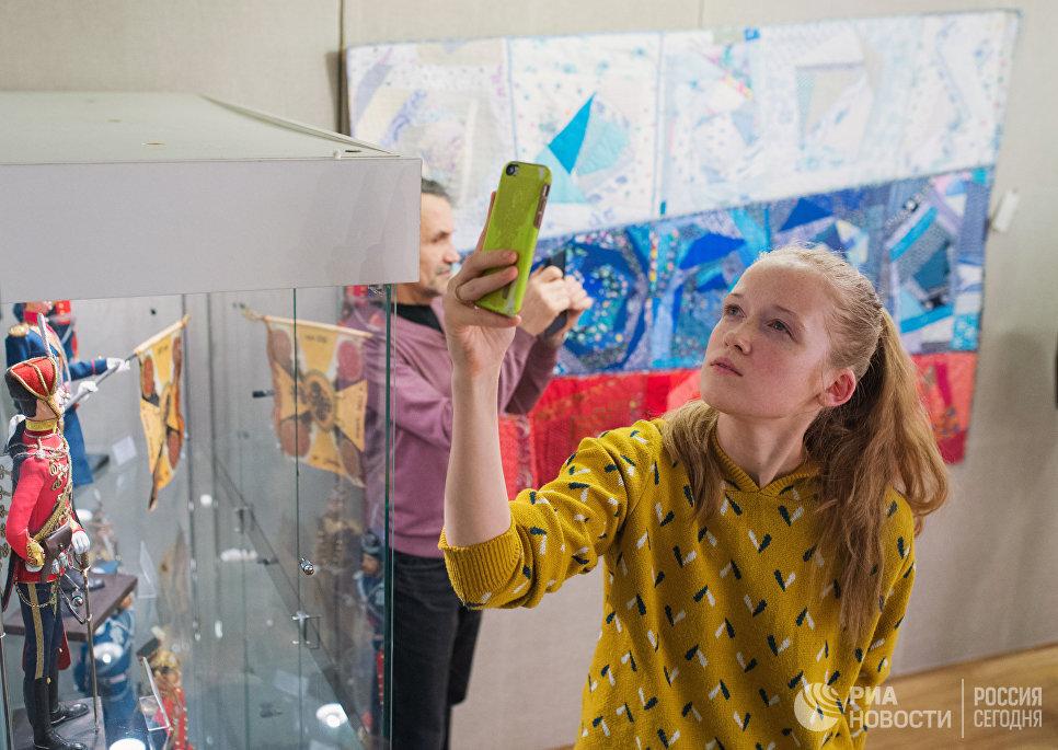 Посетительница фотографирует на открывшейся выставке Аты-баты, посвященной теме исторических традиций русской армии в ГРДНТ имени Д.В. Поленова