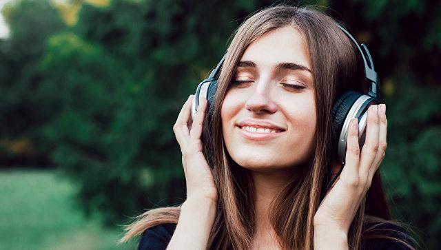 Девушка слушает музыку в наушниках. Архивное