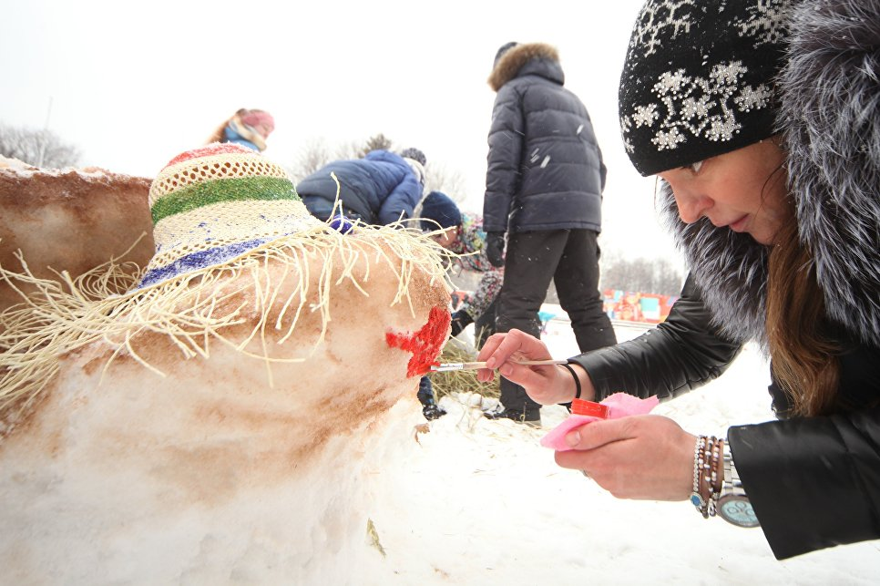 Участница украшает снежную фигуру во время Арт-битвы Снеговиков в Московском Дворце пионеров на Воробьевых горах