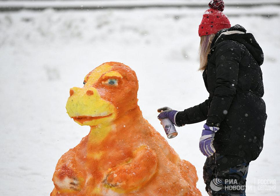 Участница наносит краску на фигуру из снега во время Арт-битвы Снеговиков в Московском Дворце пионеров на Воробьевых горах