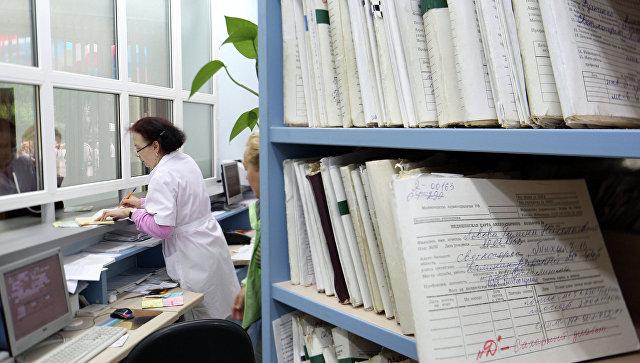 Медицинский работник выдает медицинскую карту. Архивное фото