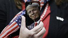 Женщина держит телефон с фотографией Дональда Трампа во время предвыборной кампании в США. Архивное фото