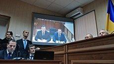 Бывший президент Украины Виктор Янукович во время видеотрансляции на экране монитора в Святошинском районном суде Киева