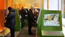 Посетители в зале банкоматов в отделении Сбербанка РФ. Архивное фото