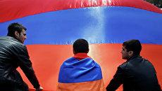 Люди на фоне флага Армении.