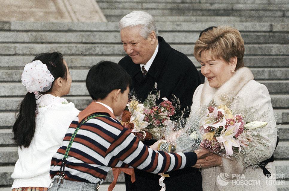 Юные жители Пекина приветствуют Президента РФ Бориса Ельцина и его супругу Наину Ельцину во время визита в КНР