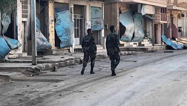 Солдаты у разрушенных в результате боевых действий домов в жилой части города Пальмира в сирийской провинции Хомс. Архивное фото